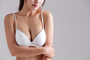 Closeup view of a young woman body chest breast with bra isolated on gray background, asian beauty